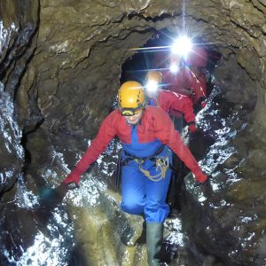 A group of cavers in a well lit passge