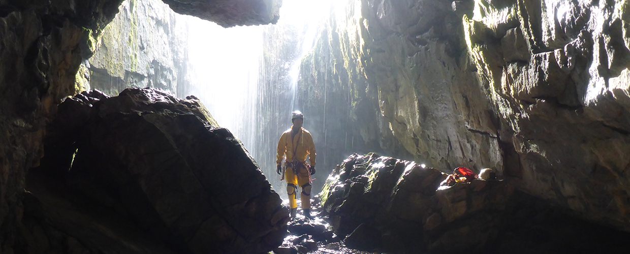 A caver by an entrance with the sunlight and water behind