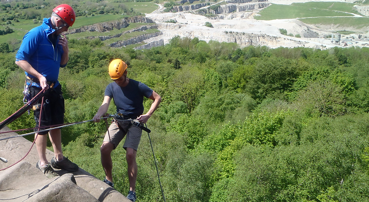abseiling off a cliff with the green canopies below