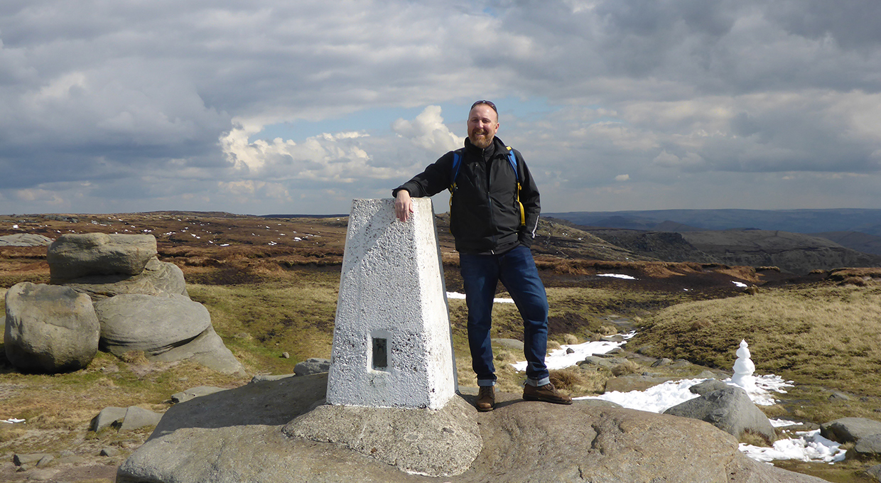 A man stood beside a white trig point on Kinder Low